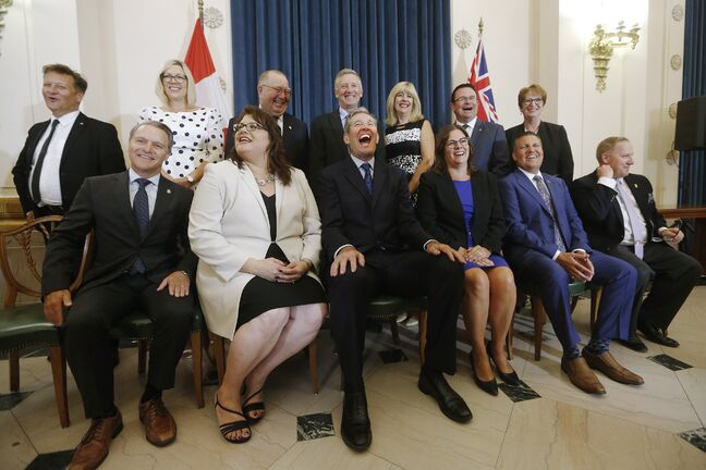 Premier Brian Pallister, centre, and his ministers laugh during a team photo after he announced a cabinet shuffle Wednesday.