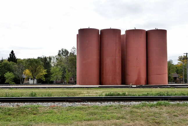 Eight large silos rise above the tree line between the tracks on the BNSF Railway line property close to Mathers Ave and Lindsay St. In River Heights.