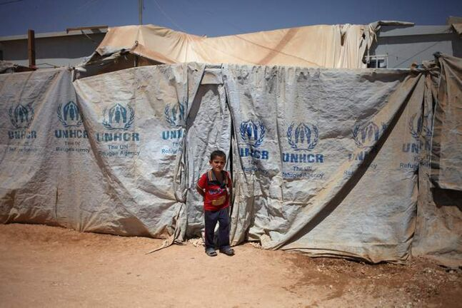 A Syrian refugee boy stands in front of his family's makeshift home at Zaatari Syrian refugee camp, in Mafraq, Jordan, in August. More than 2 million Syrians have fled the country's two-and-a-half year conflict. Jordan hosts more than 554,000 refugees.