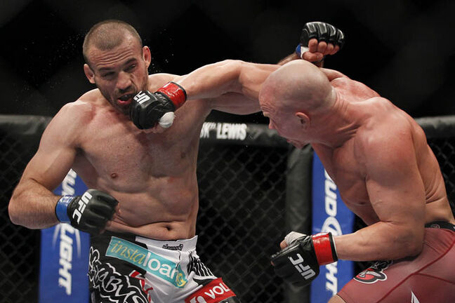 Ryan Jimmo's right hook connects to the face of Igor Pokrajac during their light heavyweight bout.