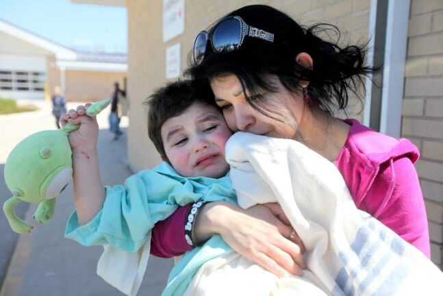 Savannah Malyon embraces her son, Nathaniel, as they leave the Portage hospital Saturday afternoon.