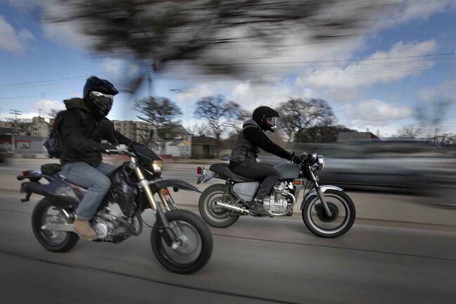 James Lowen (left) and Steve Orvis ride their motorcycles down Main Street in Winnipeg Saturday. There was a motorcycle safety rally at the legislature Saturday.