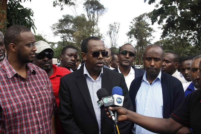 Somalia's ambassador to Kenya, Mohamed Ali Nur, centre,speaks to journalists during the burial of a 41-year-old Somali man and an 18-year-old Asian woman in Nairobi, Kenya Sunday. Both of them were killed during Saturday's mall shooting in Nairobi.