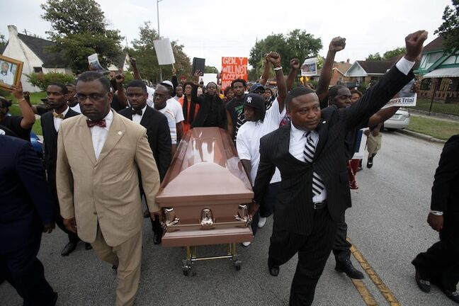 People participate in a demonstration led by activist Quanell X, right, in reaction to the acquittal of neighborhood watch member George Zimmerman Monday, July 15, 2013, in Houston. The protest began at the Byrd Funeral Home on Wheeler and ended by blocking the South Freeway at the Southmore overpass. Thousands of demonstrators from across the country — chanting, praying and fighting tears — protested a jury's decision to clear Zimmerman in the 2012 shooting death of Trayvon Martin, and organizers say they'll try to maintain the momentum with vigils next weekend. (AP Photo/Houston Chronicle, Eric Kayne)