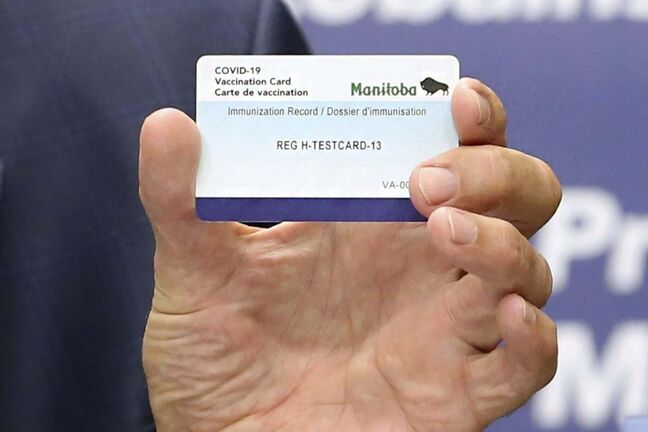 Premier Brian Pallister shows off a vaccination card. (Kevin King / Pool files)</p>