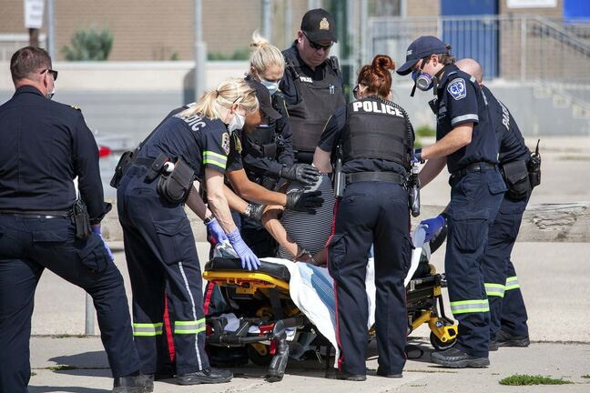 DANIEL CRUMP / WINNIPEG FREE PRESS FILES</p><p>Winnipeg Police officers and members of the Winnipeg Fire Paramedic Service tend to a handcuffed and hooded person. </p>