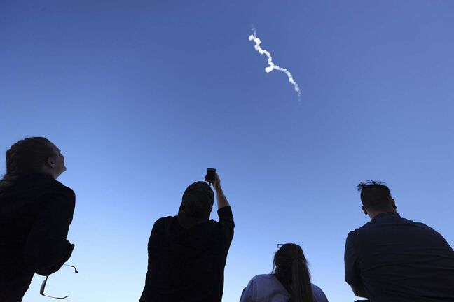 People watch as Blue Origin's New Shepard flies toward space carrying 90-year-old Star Trek actor William Shatner and three other civilians on Wednesday, Oct. 13, 2021 near Van Horn, Texas. (Mario Tama/Getty Images/TNS)</p>