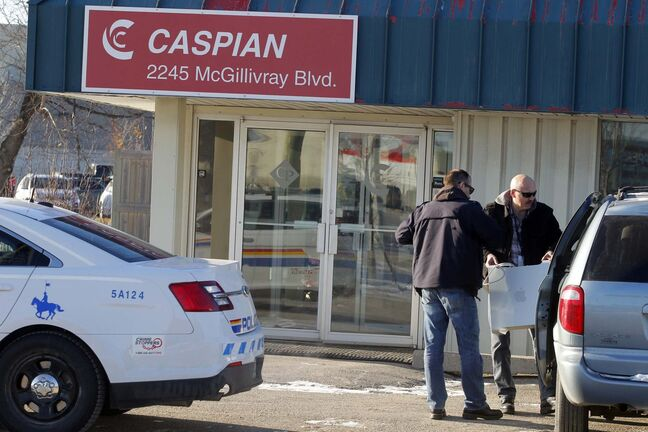 RCMP remove computer equipment from the Caspian office on McGillivray Boulevard in 2014.