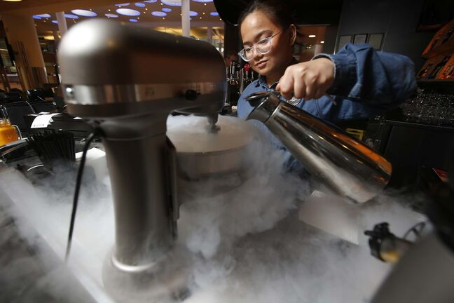 Bartender Princess Camia pours liquid nitrogen to make Maple Bacon ice cream at Flight Club restaurant at the Winnipeg airport. (John Woods photos / Winnipeg Free Press)
