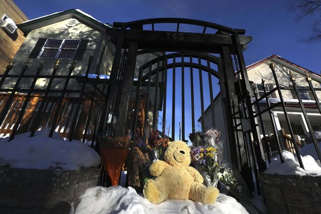 Flowers and a teddy bear serve as a memorial on the steps to the gate of the family's home on McGee Street. (Ruth Bonneville / Winnipeg Free Press)</p>