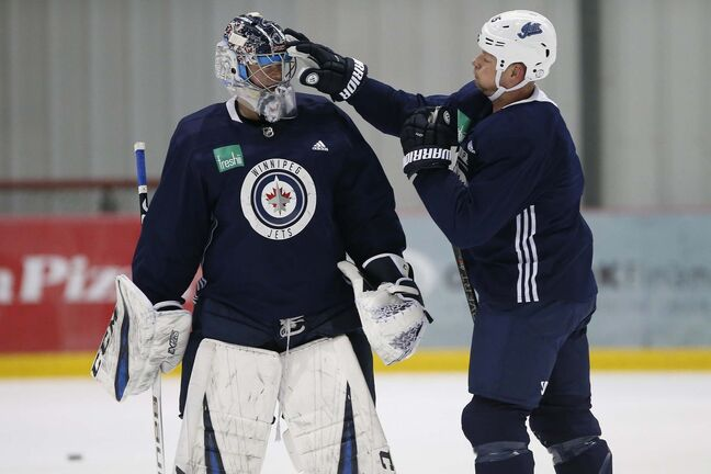 Winnipeg Jets' Matt Hendricks (15) jokes with goaltender Eric Comrie (1) during practice prior to their first round of NHL playoff action against the St. Louis Blues in Winnipeg, Monday, April 8, 2019. THE CANADIAN PRESS/John Woods</p>