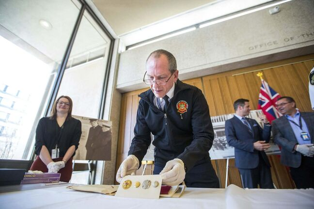 Fire Paramedic Service Chief John Lane opens a time capsule on Tuesday from 1965. (Mikaela MacKenzie / Winnipeg Free Press)