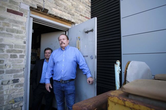 Robert McDonald, owner of Surplus Direct Liquidation, and his lawyer John Prystanski (left), in the doorway that doesn't exist according to the city. (Daniel Crump / Winnipeg Free Press)</p>