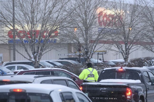 A police officer directs traffic outside of Costco on St. James Street Friday as rush hour traffic starts to pick up. (Mike Sudoma / Winnipeg Free Press)