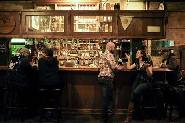 MIKE SUDOMA / WINNIPEG FREE PRESS</p><p>Patrons at the Whiskey Bar inside the Toad in the Hole enjoy drinks and conversation before the iconic bar moves in to its new home across the street in January.</p>