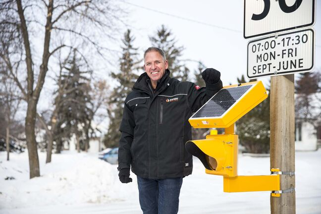 Chuck Lewis, owner of Expert Electric, decided to stop waiting for the city and installed a flashing light in a school zone on his own. (Mikaela MacKenzie / Winnipeg Free Press)