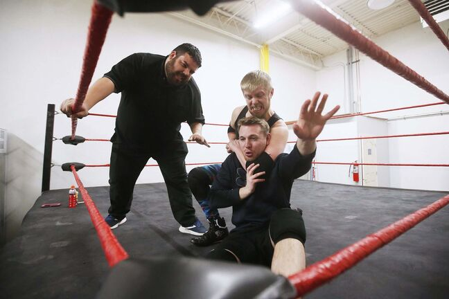 Pro wrestler A.J. Sanchez instructs as improviser George Hudson puts Steven Stashko into a chin lock during training. The performative link between acting and wrestling is a natural one. (John Woods / Winnipeg Free Press)