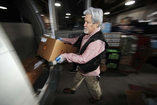 Volunteer Carlos Santistevan loads a box of food into the back of a van at the branch of the Volunteers of America as daily demands for food increase while most vulnerable individuals and families shelter inside to reduce the spread of the new coronavirus Monday, March 23, 2020, in Denver. According to the World Health Organization, most people recover in about three to six weeks depending on the severity of the COVID-19 illness. (AP Photo/David Zalubowski)</p>