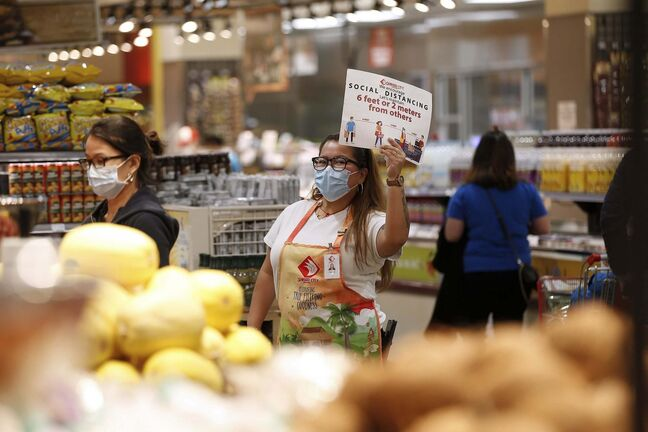 JOHN WOODS / WINNIPEG FREE PRESS</p><p>Clarchel Robles walks around the store and holds up a sign and kindly announces physical distance rules at Seafood City in Winnipeg Thursday, April 23, 2020. Seafood City have taken great steps to ensure the safety of their customers and staff.</p>