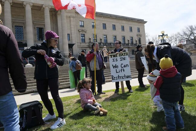 Daniel Crump / Winnipeg Free Press</p><p>Kids play in front of people holding signs at an anti-lockdown protest at the Manitoba Legislature. Social distancing and other safety protocols were not followed, or enforced. May 9, 2020.</p>