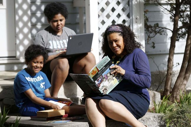 Zilla Jones sits on her front steps as her children Kamil, 9, left, and Jericho, 12, read school books. Jones, who is a full-time lawyer, says two months into the distance learning routine, parents are getting exhausted as they try to balance work and homeschool. (John Woods / Winnipeg Free Press)