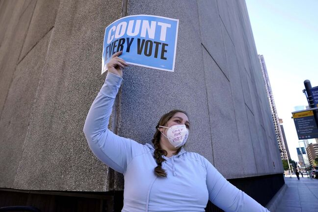 A protester in Houston calls for all votes to be counted. (David J. Phillip / The Associated Press)