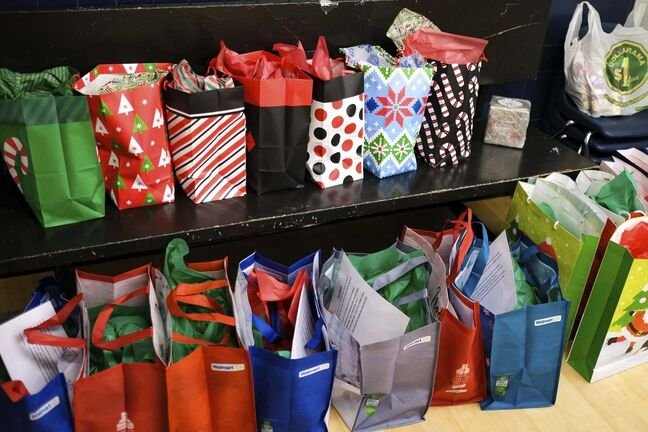 Daniel Crump / Winnipeg Free Press. Christmas gifts are lined up for participants at the Rossbrook House childcare programs. Because of the pandemic and shopping restrictions each gift bag contains creative DIY crafts that use essential items still being sold in stores. December 16, 2020.</p>