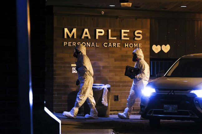Members of the Winnipeg Police Identification Unit dressed in protective equipment enter the Maples Personal Care Home in November. (Daniel Crump / Winnipeg Free Press files)</p>