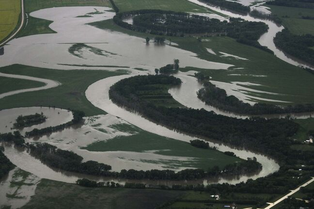 Heavy rains in western Manitoba and Saskatchewan recently have raised the level of the Assiniboine River causing it to overflow its banks flooding roads and farmers fields. Aerial photo's east of Portage la Prairie area. July 08, 2014 Ruth Bonneville / Winnipeg Free Press</p>