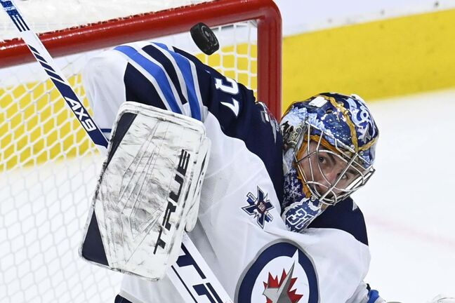 Winnipeg Jets goaltender Connor Hellebuyck (37) makes a stop against the Toronto Maple Leafs during first period NHL action in Toronto on Thursday, March 11, 2021. THE CANADIAN PRESS/Frank Gunn</p>