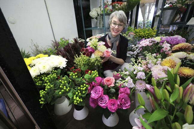 RUTH BONNEVILLE / WINNIPEG FREE PRESS Biz - Norwood Florist Photo of Michele Pitre, owner of Norwood Florist Design Studio, scene through the doors of her fridge full of beautiful flowers as she puts together a bouquet for a customer on Tuesday. Subject: Story on pandemic supply chain issues that florists are facing heading into Mothers' Day, the busiest week of the year for the industry. Business has been up by 30 per cent during the past year because people are sending more flowers since they can't meet in person. But Pitre at Norwood Florists asks customers to be patient because sometimes she doesn't even know what she's getting form the wholesalers April 27, 2021</p>