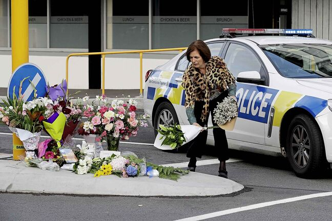 A woman places flowers at a make-shift memorial near the mosque in Christchurch, New Zealand, Saturday, March 16, 2019, where one of the mass shootings occurred yesterday. (AP Photo/Mark Baker)