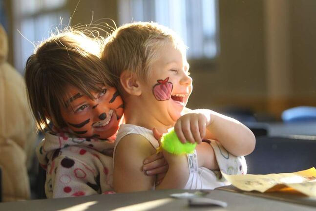 Seven year old Elizabeth Terry (left, Tiger face) giggles and tickles her friend Maci Jacobs - 3 and a half, as they open and  play with gifts given out to them at the annual Salvation Army breakfast Saturday morning.  Dec 7, 2013 Ruth Bonneville / Winnipeg Free Press
