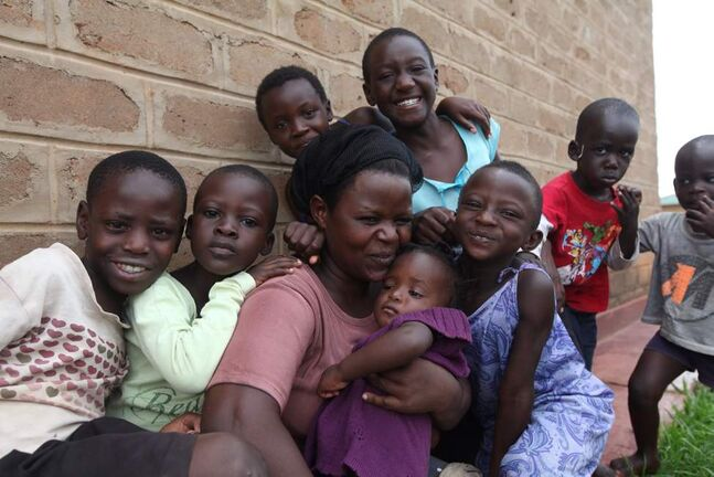 A foster mom is surrounded by her eight children outside her home in Suubi Children's Village in southern Uganda.  Many Watoto mothers are widowed or abandoned and are eager to have a family and a home.  Some have children of their own that they bring with them to live in the village that is fully supported by Watoto sponsors and donations. 