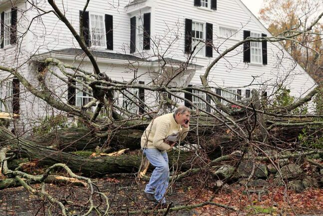 John Constantine makes his way out of his house after winds from Hurricane Sandy toppled a tree fell onto it in Andover, Mass. (AP Photo/Winslow Townson)
