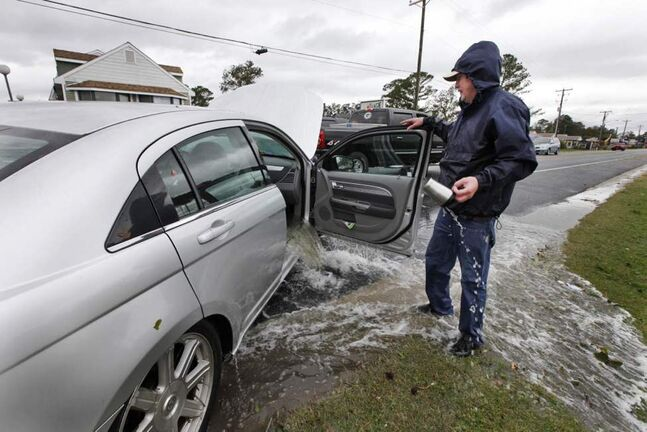 Glenn Heartley watches floodwaters from superstorm Sandy pour out of his car after it was pulled out of a creek in Chincoteague, Va., Tuesday. Heartley and his wife were swept off the road into a shallow creek during Monday's storm. (AP Photo/Steve Helber)