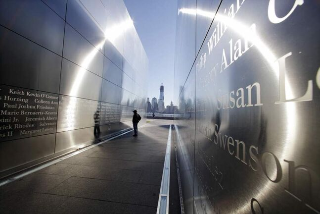 A person stops to read names in New Jersey's memorial to the 749 people from the state lost during the Sept. 11 terrorist attacks on the World Trade Center, as One World Trade Center, now up to 104 floors, looms in the distance across the Hudson River in Jersey City, N.J. (AP Photo/Mel Evans)