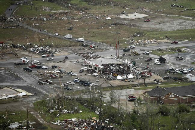 A storm-damaged convenience store, center, sits among rubble along U.S. Highway 64 in Vilonia, Ark., Monday, April 28, 2014, after a tornado struck the town late Sunday.