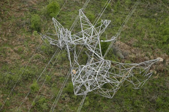 A twisted power distribution line tower is crumpled on the ground near Mayflower, Ark., Monday, April 28, 2014 after a tornado struck the town late Sunday.