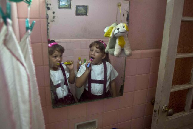 Twin sisters Asley and Aslen Velazquez, 6, prepare for school in Havana, Cuba. (AP Photo/Ramon Espinosa)