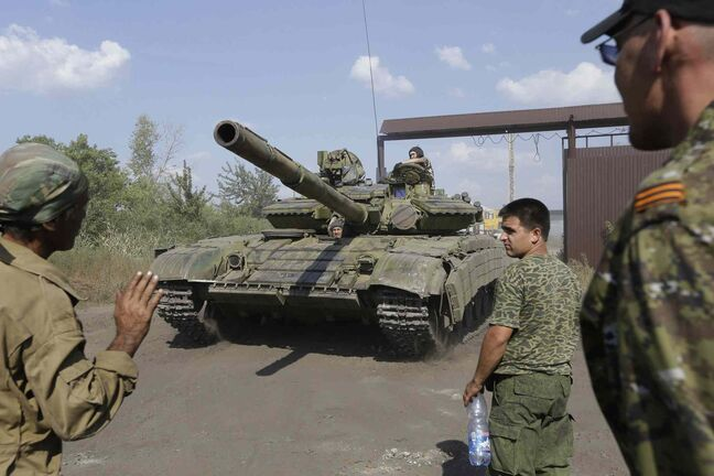 Pro-Russian rebels park a tank on their base near the town of Krasnodon, eastern Ukraine, Saturday, Aug. 16, 2014.
