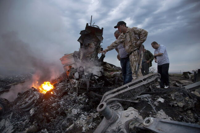 In this July 17, 2014 file photo, people inspect the crash site of a passenger plane near the village of Hrabove, Ukraine. The downing of the jet could prove to be a turning point in the country's conflict. But which way it turns depends mainly on who carried out the attack and how convincingly it can be proved to the world.
