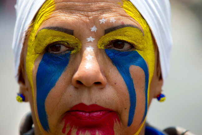 An opposition demonstrator with her face painted colours of the Venezuelan flag listens to a speech during a May Day march in Caracas. Pro-government and opposition workers measured forces in the streets of the capital with separate marches that took place to commemorate the first of May — all in the midst of political and economic crisis prevailing in the country.