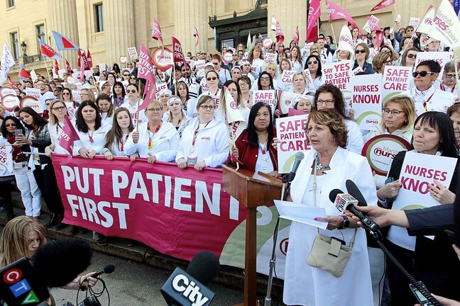 BORIS MINKEVICH / WINNIPEG FREE PRESS    Around 700 nurses and supporters converged on to the steps of the Manitoba Legislature today to protest against healthcare cuts. President of the 12,000 member Manitoba Nurses Union Sandi Mowat, right at the mic, speaks at the event. JANE GERSTER STORY.  May 2, 2018