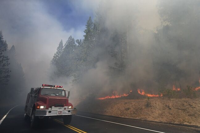 A fire truck drives past burning trees near Yosemite National Park, Calif., on Monday.