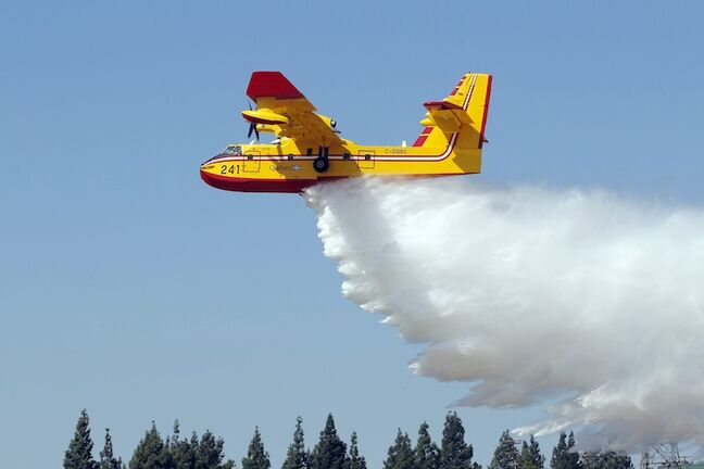 A Canadian Bombardier CL-415 Super Scooper firefighting plane drops water during a demonstration at Van Nuys Airport in Los Angeles Monday.