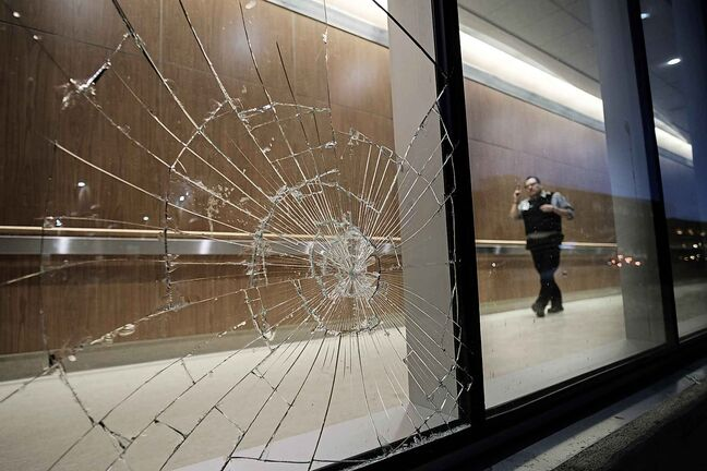 Daniel Crump / Winnipeg Free Press. A security officer walks by a broken window near the Adult Emergency entrance at Health Sciences Centre. February 28, 2018.