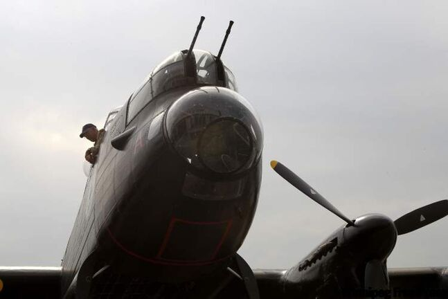 A member of the flight crew looks out a window in the cockpit of the 'Mynarski Memorial' Avro Lancaster Mk10 Bomber as it arrives at the Western Canada Aviation Museum.