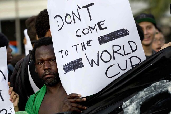 A man discourages people from attending the World Cup soccer tournament during a march demanding better public services in Rio de Janeiro. Last year, millions of people took to the streets across Brazil complaining of higher bus fares, poor public services and corruption while the country spends billions on the World Cup.
