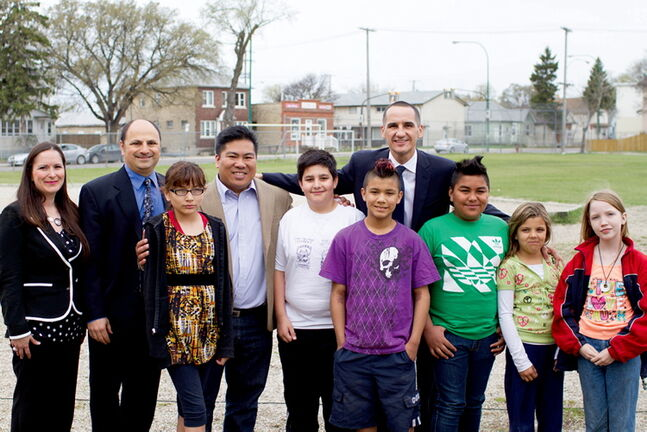 Children and Youth Opportunities Minister Kevin Chief (Back row, at right) and Point Douglas Coun. Mike Pagtakhan (centre left, in brown jacket) announce funding for a new playground at King Edward School along with students and (from left) Vice-Principal Michelle Sacco and Principal Aaron Benarroch.